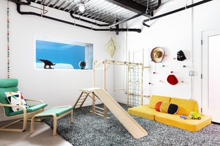 The new below-grade playroom, with its wood EZ Play Jungle Gym, doubles as a bedroom and features a window that looks into the pool.
