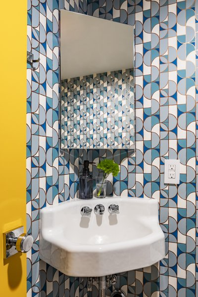 The powder room gets its geometric edge from Heath Ceramics for Hygge and West wallpaper.