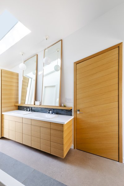 In the master bathroom, a skylight shines natural light onto Cle Tile and lighting fixtures by Rejuvenation. Paul Rene designed the custom white oak vanity and mirrors.