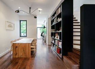 On the ground floor adjacent to the open living and dining room, a tall black bookcase defines the stair, housing the owners' colourful books and small collectibles.