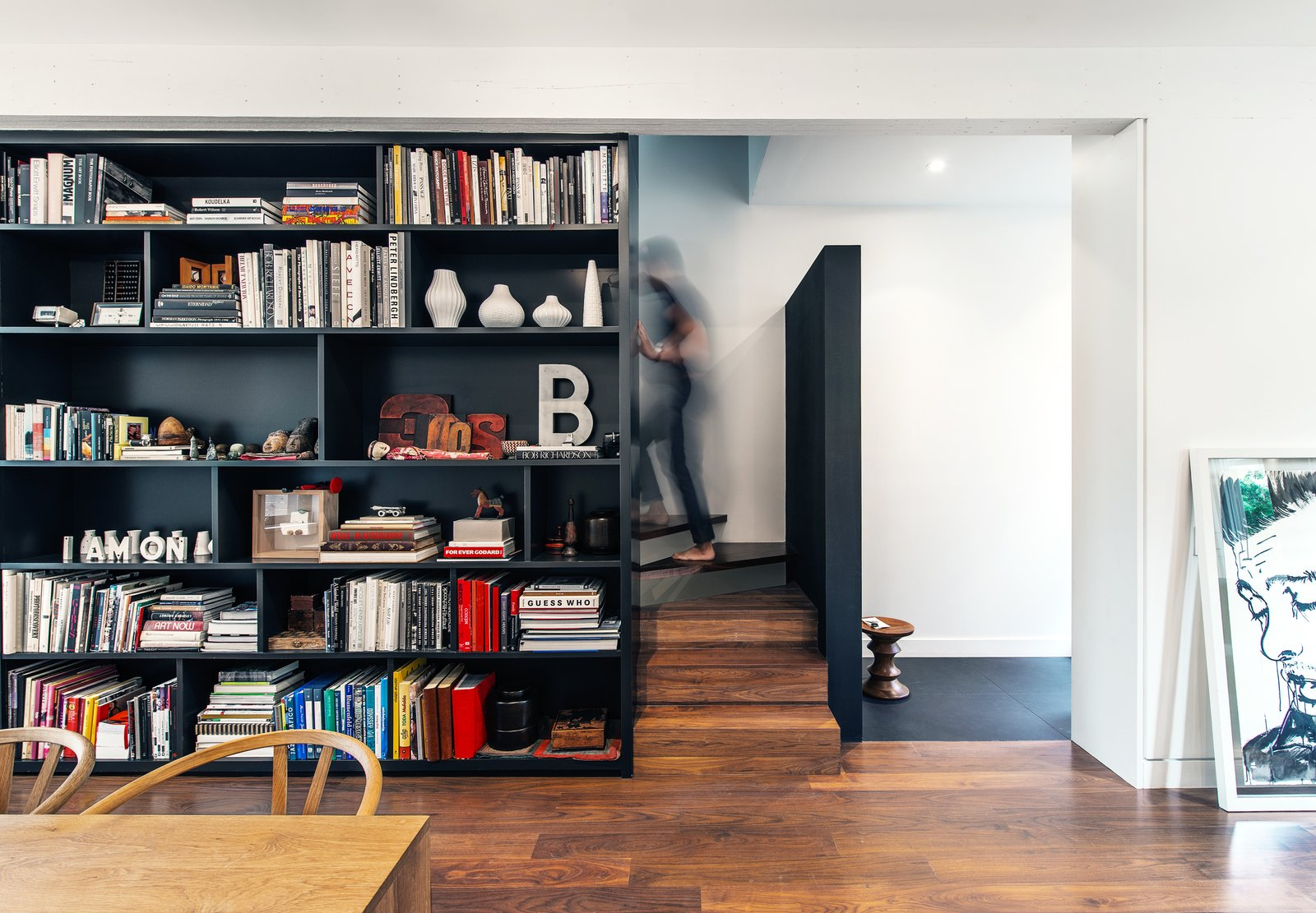 Storage Room, Shelves Storage Type, and Under Stairs Storage Type Upon entry into the vestibule, visitors are greeted by a textured black wall, stopping short of the ceiling and allowing for a glimpse up the stair  Contrast House