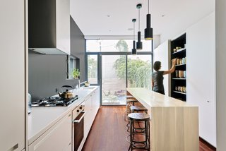 The long, narrow kitchen, at only 11 feet wide, is delineated by the 'tapas bar' island, a wall of floor to ceiling concealed cabinetry, and a long white counter contrasting with a charcoal wall.