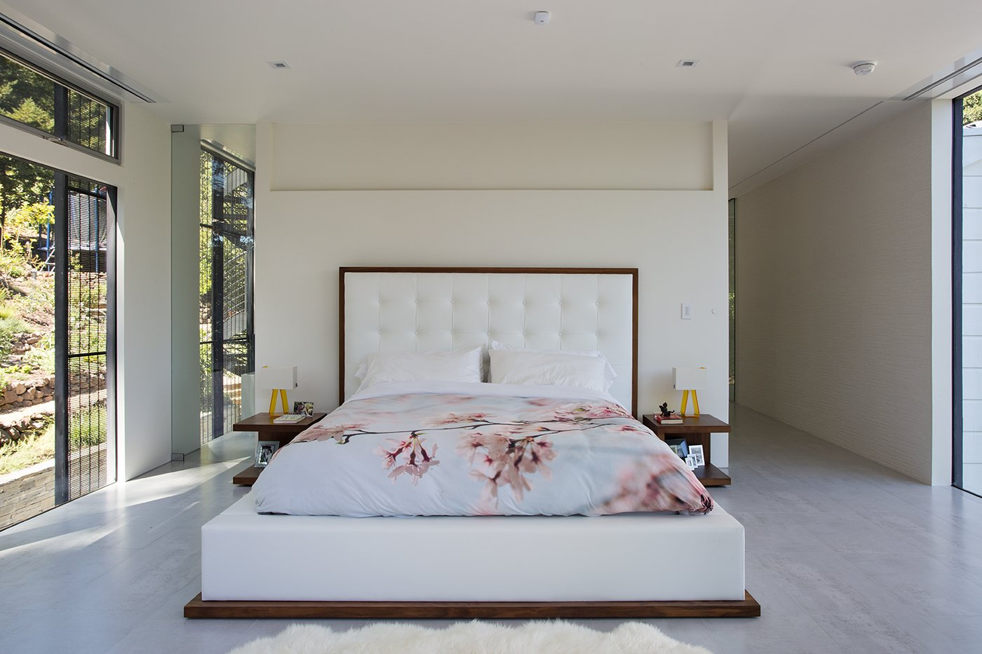 Bedroom and Bed Minimal Modern Addition  Sebastian and Tanja DiGrande's quest for natural light and open, modern design led them to Klopf Architecture in San Francisco. Working hand-in-hand with homeowner/designer Tanja DiGrande, Klopf collaborated on a modern addition to the rear of a traditional-style home. The idea was to depart from the original style completely to draw a distinction between the original house and any later additions, as well as observe a very minimal, clean, gallery-like modern style against which changing daylight, art, furniture, and of course the people provide the color and motion.  With its dark gray stuccoed walls, dark steel railing, and floor-to-ceiling windows, the exterior of the addition is at the same time an open, modern box as well as a receding volume that acts almost as a backdrop for the house, receding visually out of respect for the original home. From the interior, windows bring in nature and views from all around the lush property. They also allow views of the original house. Up on the roof deck the views magnify. The owners use a boom and crank to bring up food and drinks when entertaining!  Inside, the simple clean-lined spaces showcase the couple's minimal, modern taste. The open bathroom epitomizes the clean, minimal style of the addition. On the exterior, steel elements bring a more industrial modern feeling to the addition from the rear.   Klopf Architecture