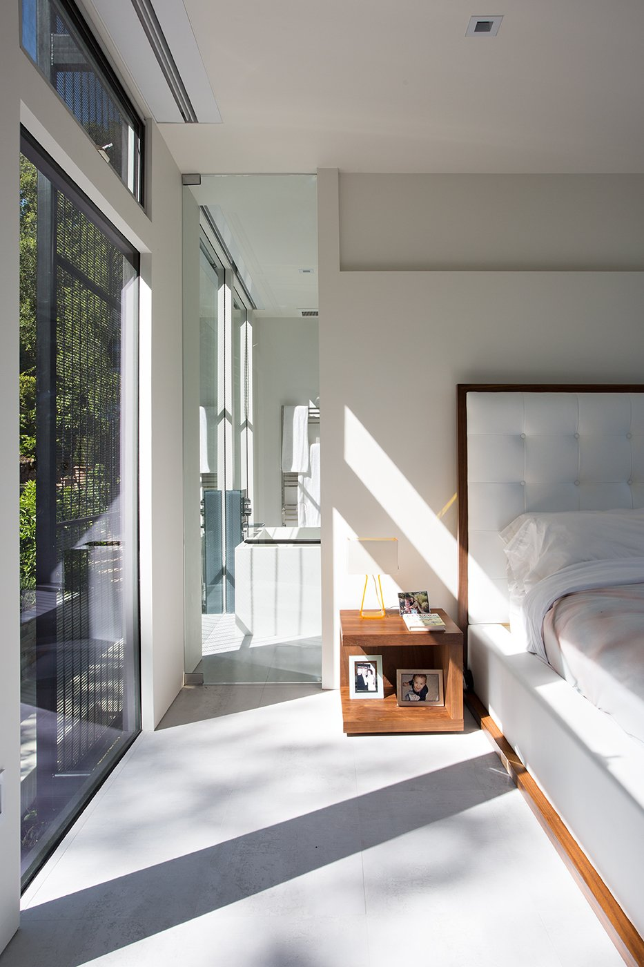 Bedroom, Bed, and Night Stands Minimal Modern Addition  Sebastian and Tanja DiGrande's quest for natural light and open, modern design led them to Klopf Architecture in San Francisco. Working hand-in-hand with homeowner/designer Tanja DiGrande, Klopf collaborated on a modern addition to the rear of a traditional-style home. The idea was to depart from the original style completely to draw a distinction between the original house and any later additions, as well as observe a very minimal, clean, gallery-like modern style against which changing daylight, art, furniture, and of course the people provide the color and motion.  With its dark gray stuccoed walls, dark steel railing, and floor-to-ceiling windows, the exterior of the addition is at the same time an open, modern box as well as a receding volume that acts almost as a backdrop for the house, receding visually out of respect for the original home. From the interior, windows bring in nature and views from all around the lush property. They also allow views of the original house. Up on the roof deck the views magnify. The owners use a boom and crank to bring up food and drinks when entertaining!  Inside, the simple clean-lined spaces showcase the couple's minimal, modern taste. The open bathroom epitomizes the clean, minimal style of the addition. On the exterior, steel elements bring a more industrial modern feeling to the addition from the rear.   Klopf Architecture