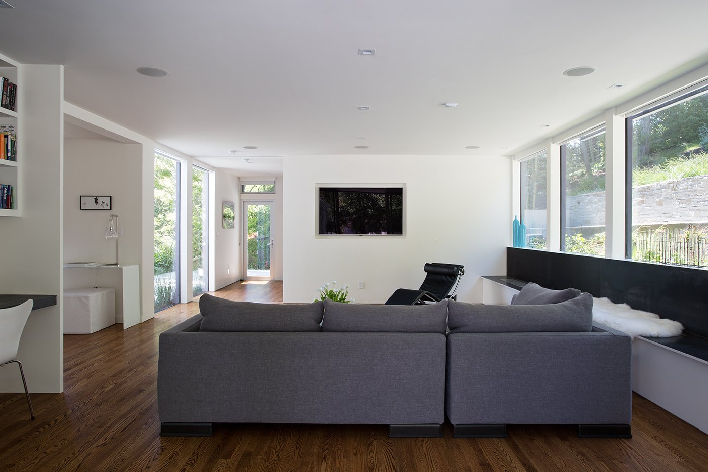 Minimal Modern Addition  Sebastian and Tanja DiGrande's quest for natural light and open, modern design led them to Klopf Architecture in San Francisco. Working hand-in-hand with homeowner/designer Tanja DiGrande, Klopf collaborated on a modern addition to the rear of a traditional-style home. The idea was to depart from the original style completely to draw a distinction between the original house and any later additions, as well as observe a very minimal, clean, gallery-like modern style against which changing daylight, art, furniture, and of course the people provide the color and motion.  With its dark gray stuccoed walls, dark steel railing, and floor-to-ceiling windows, the exterior of the addition is at the same time an open, modern box as well as a receding volume that acts almost as a backdrop for the house, receding visually out of respect for the original home. From the interior, windows bring in nature and views from all around the lush property. They also allow views of the original house. Up on the roof deck the views magnify. The owners use a boom and crank to bring up food and drinks when entertaining!  Inside, the simple clean-lined spaces showcase the couple's minimal, modern taste. The open bathroom epitomizes the clean, minimal style of the addition. On the exterior, steel elements bring a more industrial modern feeling to the addition from the rear.   Klopf Architecture
