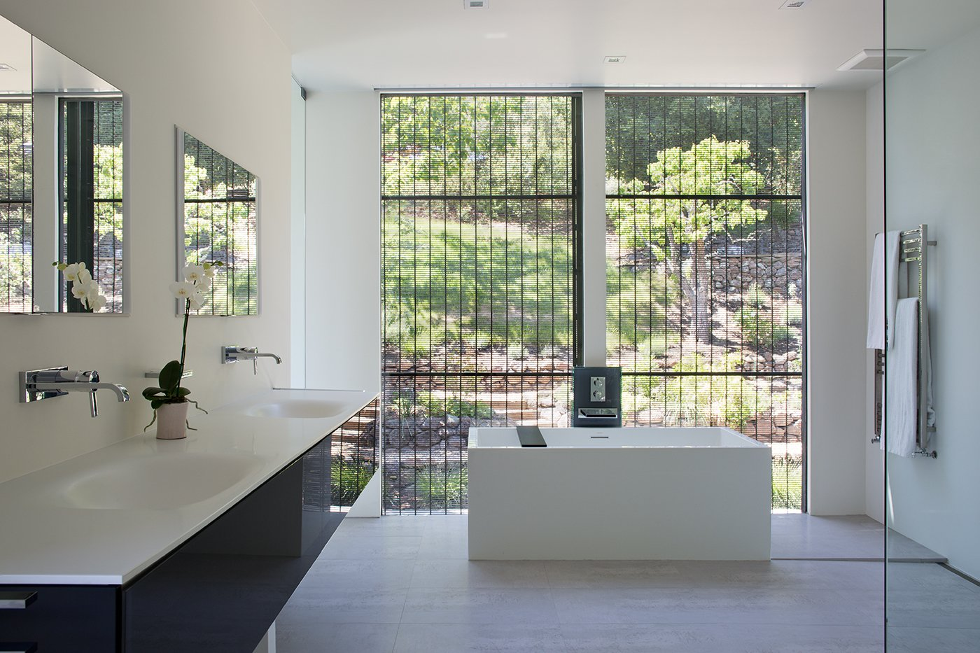Bath Room, Freestanding Tub, and Wall Mount Sink Minimal Modern Addition  Sebastian and Tanja DiGrande's quest for natural light and open, modern design led them to Klopf Architecture in San Francisco. Working hand-in-hand with homeowner/designer Tanja DiGrande, Klopf collaborated on a modern addition to the rear of a traditional-style home. The idea was to depart from the original style completely to draw a distinction between the original house and any later additions, as well as observe a very minimal, clean, gallery-like modern style against which changing daylight, art, furniture, and of course the people provide the color and motion.  With its dark gray stuccoed walls, dark steel railing, and floor-to-ceiling windows, the exterior of the addition is at the same time an open, modern box as well as a receding volume that acts almost as a backdrop for the house, receding visually out of respect for the original home. From the interior, windows bring in nature and views from all around the lush property. They also allow views of the original house. Up on the roof deck the views magnify. The owners use a boom and crank to bring up food and drinks when entertaining!  Inside, the simple clean-lined spaces showcase the couple's minimal, modern taste. The open bathroom epitomizes the clean, minimal style of the addition. On the exterior, steel elements bring a more industrial modern feeling to the addition from the rear.   Klopf Architecture