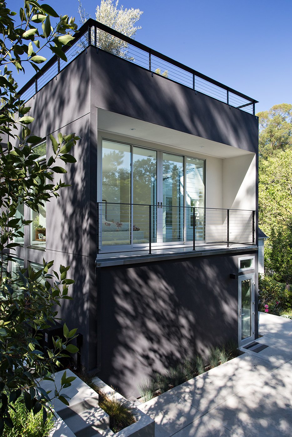 Exterior, Flat RoofLine, and House Building Type Minimal Modern Addition  Sebastian and Tanja DiGrande's quest for natural light and open, modern design led them to Klopf Architecture in San Francisco. Working hand-in-hand with homeowner/designer Tanja DiGrande, Klopf collaborated on a modern addition to the rear of a traditional-style home. The idea was to depart from the original style completely to draw a distinction between the original house and any later additions, as well as observe a very minimal, clean, gallery-like modern style against which changing daylight, art, furniture, and of course the people provide the color and motion.  With its dark gray stuccoed walls, dark steel railing, and floor-to-ceiling windows, the exterior of the addition is at the same time an open, modern box as well as a receding volume that acts almost as a backdrop for the house, receding visually out of respect for the original home. From the interior, windows bring in nature and views from all around the lush property. They also allow views of the original house. Up on the roof deck the views magnify. The owners use a boom and crank to bring up food and drinks when entertaining!  Inside, the simple clean-lined spaces showcase the couple's minimal, modern taste. The open bathroom epitomizes the clean, minimal style of the addition. On the exterior, steel elements bring a more industrial modern feeling to the addition from the rear.   Klopf Architecture