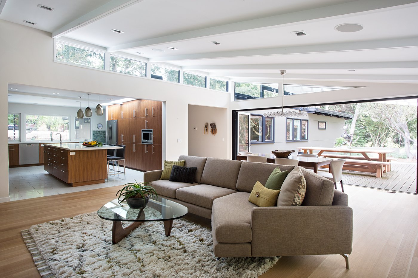 """Living Room, Sofa, Chair, Rug Floor, and Light Hardwood Floor Lafayette Mid Century Modern Remodel   The owners of this property had been away from the Bay Area for many years, and looked forward to returning to an elegant mid-century modern house. The one they bought was anything but that. Faced with a """"remuddled"""" kitchen from one decade, a haphazard bedroom / family room addition from another, and an otherwise disjointed and generally run-down mid-century modern house, the owners asked Klopf Architecture and Envision Landscape Studio to re-imagine this house and property as a unified, flowing, sophisticated, warm, modern indoor / outdoor living space for a family of five.   Opening up the spaces internally and from inside to out was the first order of business. The formerly disjointed eat-in kitchen with 7 foot high ceilings were opened up to the living room, re-oriented, and replaced with a spacious cook's kitchen complete with a row of skylights bringing light into the space. Adjacent the living room wall was completely opened up with La Cantina folding door system, connecting the interior living space to a new wood deck that acts as a continuation of the wood floor. People can flow from kitchen to the living / dining room and the deck seamlessly, making the main entertainment space feel at once unified and complete, and at the same time open and limitless.   Klopf opened up the bedroom with a large sliding panel, and turned what was once a large walk-in closet into an office area, again with a large sliding panel. The master bathroom has high windows all along one wall to bring in light, and a large wet room area for the shower and tub. The dark, solid roof structure over the patio was replaced with an open trellis that allows plenty of light, brightening the new deck area as well as the interior of the house. Located in Lafayette, CA this remodeled single-family house is 3,363 square foot, 4 bedroom, and 3.5 bathroom.   Klopf Architecture"""