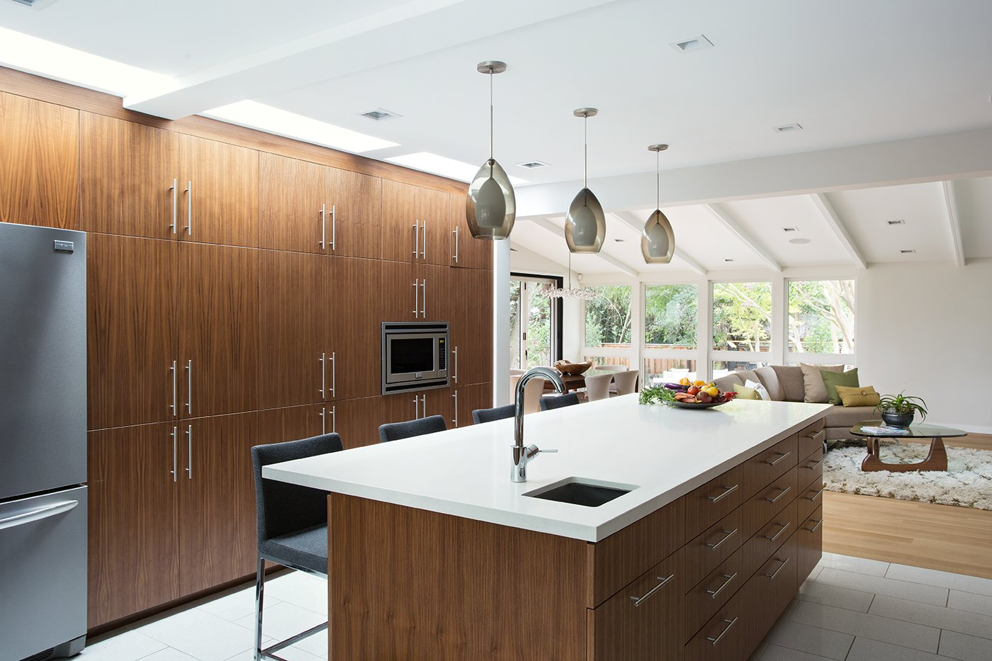 """Kitchen, Wood Cabinet, Refrigerator, Wall Oven, and Pendant Lighting Lafayette Mid Century Modern Remodel   The owners of this property had been away from the Bay Area for many years, and looked forward to returning to an elegant mid-century modern house. The one they bought was anything but that. Faced with a """"remuddled"""" kitchen from one decade, a haphazard bedroom / family room addition from another, and an otherwise disjointed and generally run-down mid-century modern house, the owners asked Klopf Architecture and Envision Landscape Studio to re-imagine this house and property as a unified, flowing, sophisticated, warm, modern indoor / outdoor living space for a family of five.   Opening up the spaces internally and from inside to out was the first order of business. The formerly disjointed eat-in kitchen with 7 foot high ceilings were opened up to the living room, re-oriented, and replaced with a spacious cook's kitchen complete with a row of skylights bringing light into the space. Adjacent the living room wall was completely opened up with La Cantina folding door system, connecting the interior living space to a new wood deck that acts as a continuation of the wood floor. People can flow from kitchen to the living / dining room and the deck seamlessly, making the main entertainment space feel at once unified and complete, and at the same time open and limitless.   Klopf opened up the bedroom with a large sliding panel, and turned what was once a large walk-in closet into an office area, again with a large sliding panel. The master bathroom has high windows all along one wall to bring in light, and a large wet room area for the shower and tub. The dark, solid roof structure over the patio was replaced with an open trellis that allows plenty of light, brightening the new deck area as well as the interior of the house. Located in Lafayette, CA this remodeled single-family house is 3,363 square foot, 4 bedroom, and 3.5 bathroom.   Klopf Architecture"""