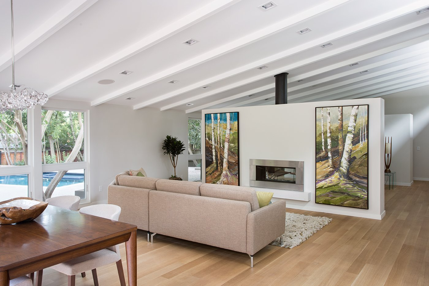 """Living Room, Sofa, Light Hardwood Floor, and Gas Burning Fireplace Lafayette Mid Century Modern Remodel   The owners of this property had been away from the Bay Area for many years, and looked forward to returning to an elegant mid-century modern house. The one they bought was anything but that. Faced with a """"remuddled"""" kitchen from one decade, a haphazard bedroom / family room addition from another, and an otherwise disjointed and generally run-down mid-century modern house, the owners asked Klopf Architecture and Envision Landscape Studio to re-imagine this house and property as a unified, flowing, sophisticated, warm, modern indoor / outdoor living space for a family of five.   Opening up the spaces internally and from inside to out was the first order of business. The formerly disjointed eat-in kitchen with 7 foot high ceilings were opened up to the living room, re-oriented, and replaced with a spacious cook's kitchen complete with a row of skylights bringing light into the space. Adjacent the living room wall was completely opened up with La Cantina folding door system, connecting the interior living space to a new wood deck that acts as a continuation of the wood floor. People can flow from kitchen to the living / dining room and the deck seamlessly, making the main entertainment space feel at once unified and complete, and at the same time open and limitless.   Klopf opened up the bedroom with a large sliding panel, and turned what was once a large walk-in closet into an office area, again with a large sliding panel. The master bathroom has high windows all along one wall to bring in light, and a large wet room area for the shower and tub. The dark, solid roof structure over the patio was replaced with an open trellis that allows plenty of light, brightening the new deck area as well as the interior of the house. Located in Lafayette, CA this remodeled single-family house is 3,363 square foot, 4 bedroom, and 3.5 bathroom.   Klopf Architecture"""