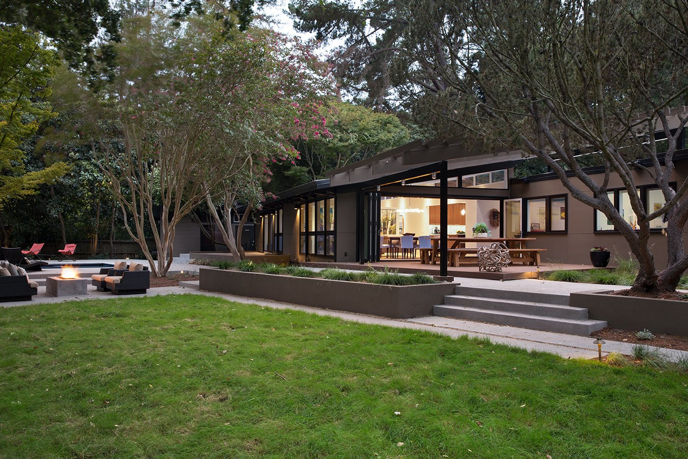 "Outdoor, Grass, and Back Yard Lafayette Mid Century Modern Remodel   The owners of this property had been away from the Bay Area for many years, and looked forward to returning to an elegant mid-century modern house. The one they bought was anything but that. Faced with a ""remuddled"" kitchen from one decade, a haphazard bedroom / family room addition from another, and an otherwise disjointed and generally run-down mid-century modern house, the owners asked Klopf Architecture and Envision Landscape Studio to re-imagine this house and property as a unified, flowing, sophisticated, warm, modern indoor / outdoor living space for a family of five.   Opening up the spaces internally and from inside to out was the first order of business. The formerly disjointed eat-in kitchen with 7 foot high ceilings were opened up to the living room, re-oriented, and replaced with a spacious cook's kitchen complete with a row of skylights bringing light into the space. Adjacent the living room wall was completely opened up with La Cantina folding door system, connecting the interior living space to a new wood deck that acts as a continuation of the wood floor. People can flow from kitchen to the living / dining room and the deck seamlessly, making the main entertainment space feel at once unified and complete, and at the same time open and limitless.   Klopf opened up the bedroom with a large sliding panel, and turned what was once a large walk-in closet into an office area, again with a large sliding panel. The master bathroom has high windows all along one wall to bring in light, and a large wet room area for the shower and tub. The dark, solid roof structure over the patio was replaced with an open trellis that allows plenty of light, brightening the new deck area as well as the interior of the house. Located in Lafayette, CA this remodeled single-family house is 3,363 square foot, 4 bedroom, and 3.5 bathroom.   Klopf Architecture"