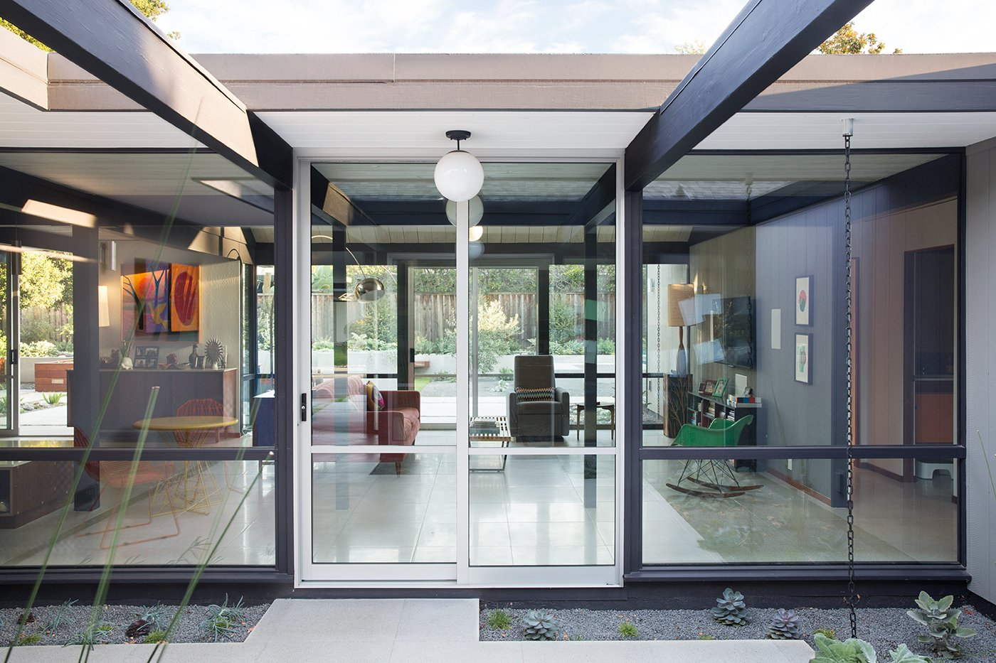 """Doors and Exterior Renewed Classic Eichler Remodel  Klopf Architecture, Growsgreen Landscape Design, and Flegel's Construction partnered to bring this mid-century atrium Eichler home up to 21st century standards. Together with the owners, Geoff Campen and the Klopf Architecture team carefully integrated elements and ideas from the mid-century period without making the space seem dated. They entrusted Klopf Architecture to respectfully expand and update the home, while still keeping it """"classic"""". The Klopf team helped them open up the kitchen, dining, and living spaces into one flowing great room, expand the master suite, replace the kitchen and bathrooms, and provide additional features like an office and powder room, all while maintaining the mid-century modern style of this Silicon Valley home.   Photo 7 of 8 in The Unsung Story of Eichler Homes and How They Helped Integrate American Neighborhoods from Klopf Architecture"""