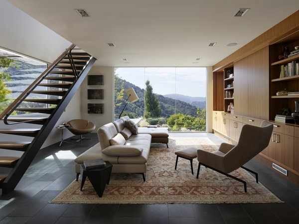 The original home occupies a prominent hilltop overlooking Silicon Valley and faces into the pristine rolling hills of a nature preserve at the end of the house receiving the new addition. Taking cues from dominant natural elements of the surrounding densely wooded hillside – boulders, bark, and leaves – SaA created a two-story addition with the visual weight needed to anchor the long axis of the extended original house. Against this, the architects balanced steel-framed stair treads and awnings that cantilever from minimal structural supports as if leaves from a slender branch.