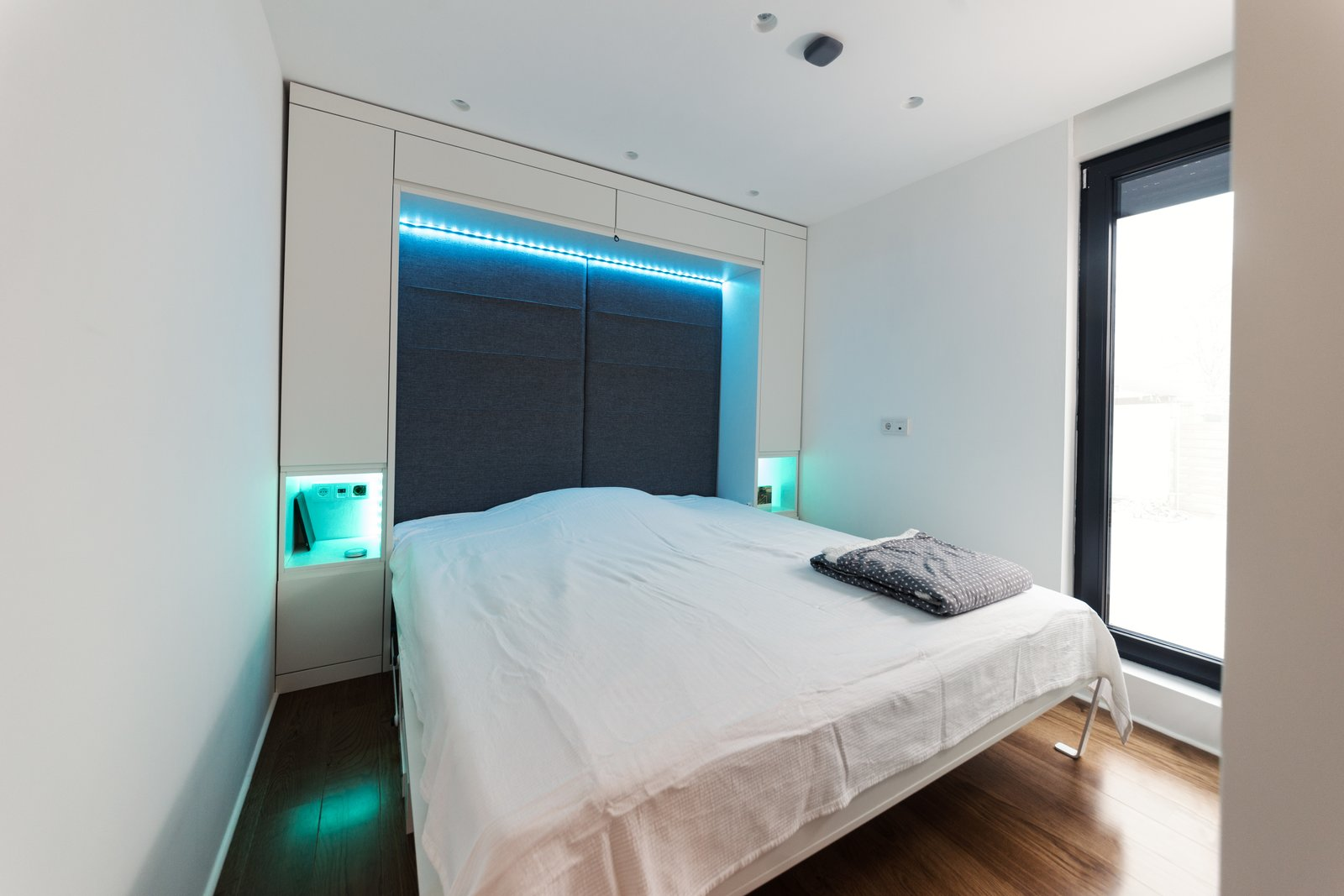 Bedroom, Bed, Storage, Dark Hardwood Floor, Accent Lighting, and Recessed Lighting Coodo integrates space-saving features like a fold-out bed.  Photo 5 of 12 in Meet the Prefab Unit That's Smart, Mobile, and Sustainable