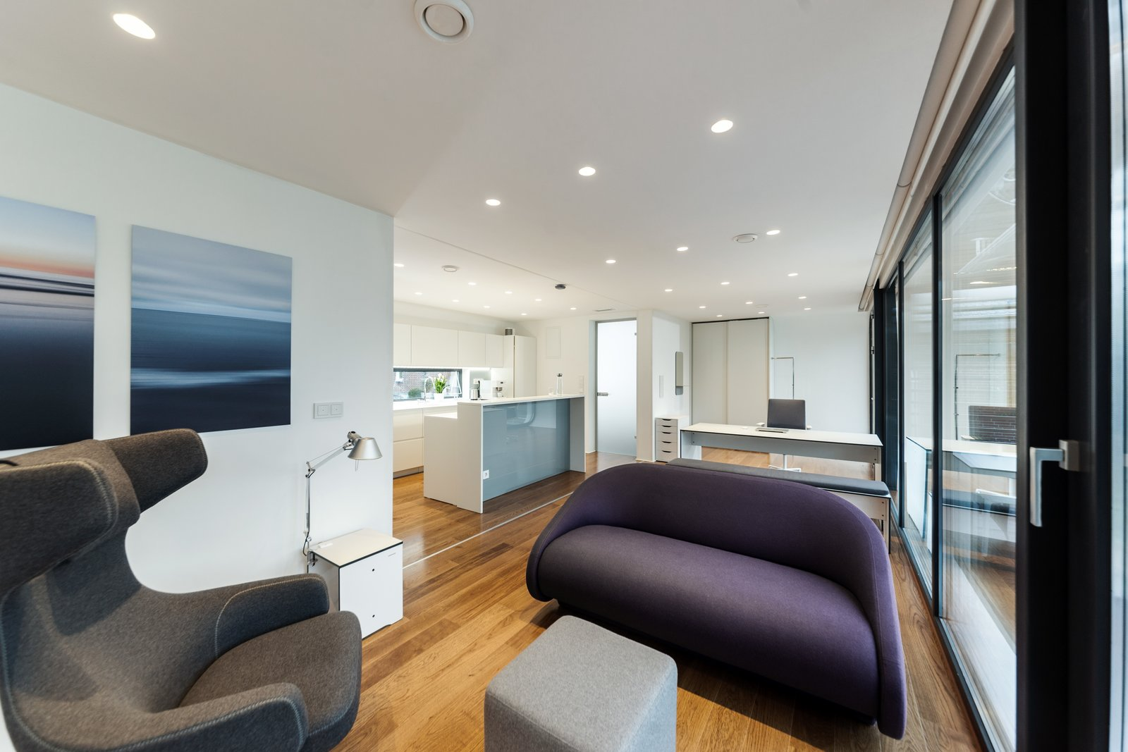 Living Room, Desk, Chair, Sofa, Recessed Lighting, Medium Hardwood Floor, Table Lighting, Bench, Ottomans, and Bar Coodo's sleek design features wireless technology.  Photo 4 of 12 in Meet the Prefab Unit That's Smart, Mobile, and Sustainable