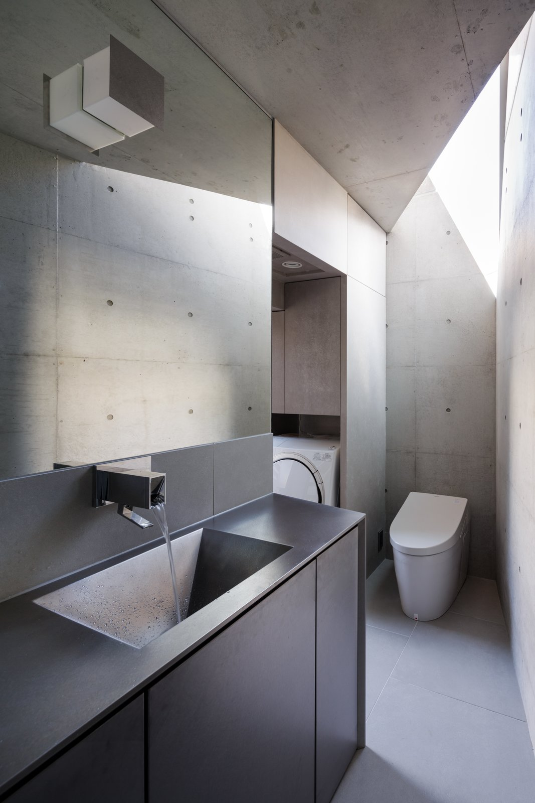 Bath Room, Undermount Sink, One Piece Toilet, Concrete Wall, and Wall Lighting The bathroom in Atelier Tekuto's concrete house in Tokyo.   Photo 16 of 16 in A Concrete Micro-House in Japan Works All the Angles