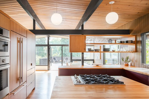 The kitchen looks out on the big open deck with expansive tree views.