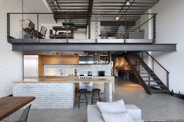 Inserting a mix of texture, raw materials and functional elements, SHED Architecture & Design was able to artfully marry the new additions with the original industrial construction in Capitol Hill Loft by using a palette of concrete brick, stainless steel plate, blackened steel, and mirror.