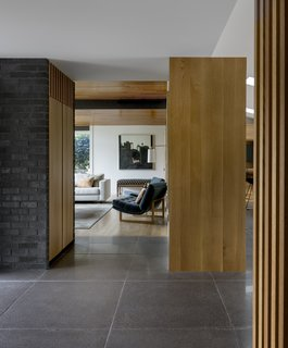 Oversized concrete tile lines the entry, kitchen, and dining room. The minimalist aesthetic juxtaposes dark and light materials.