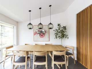 The dining room features pendant lighting, a slatted wood divider, and midcentury art selected by the homeowner. The divider encloses the space while allowing light and air to pass through.