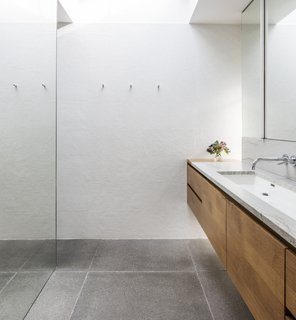 The master bath features round penny tiles and concrete tile floors.