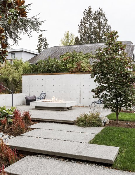 Large aggregate concrete pavers lead to the new fire pit. A concrete wall provides privacy and a sense of enclosure.