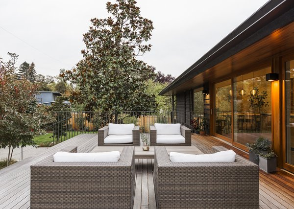 SHED reorganized the outdoor space into dedicated entertainment zones. The new deck connects directly to the kitchen via sliding doors.