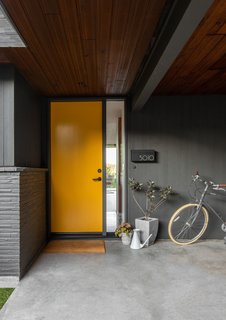 This midcentury home, originally owned by a local illustrator, needed updating, remodeling, and fortifying. Seattle-based SHED Architecture & Design tackled the project, keeping some classic features while updating others, like the front door in a semi-gloss orange.