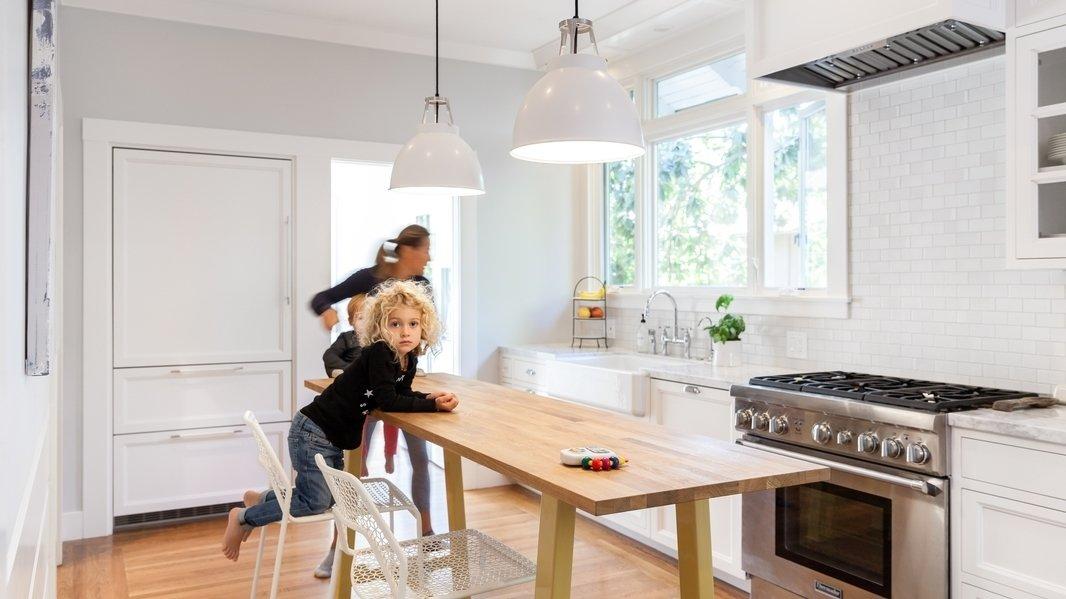 Kitchen, Pendant Lighting, Medium Hardwood Floor, Range, White Cabinet, and Marble Counter Kitchen  Photos from Land Park Drive