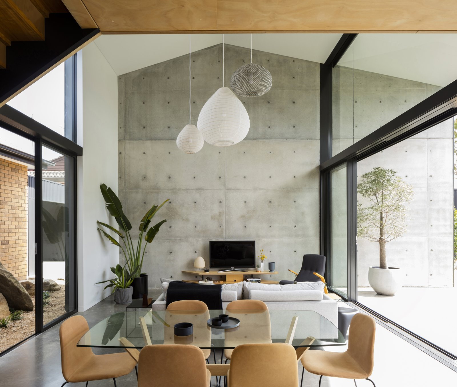 Living, Concrete, Chair, Pendant, End Tables, Shelves, Sofa, and Table Overall living area with dual aspects and connections to an interstitial garden court and rear landscaped yard beyond its concrete terrace  Best Living Concrete Pendant Photos from Binary House