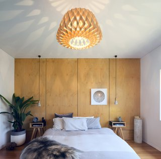An oversized geometric pendant is expertly matched to the wall behind the bed for a simple, cohesive, and impactful look.