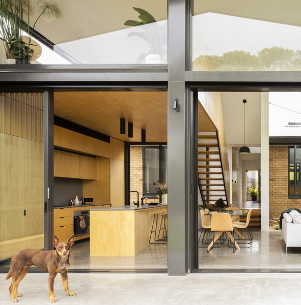 A binary play of considered honey and gray tones strongly reference the exterior yellow brick and gray metal of the two distinct structures.