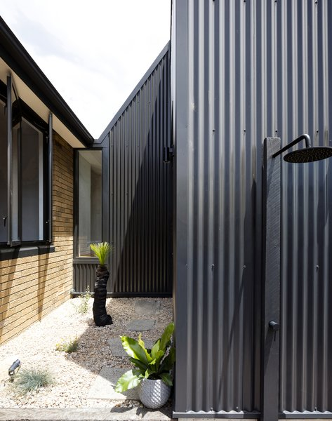 The refashioned rear of the original 1960's brick dwelling, northern courtyard secondary entry, and intermediary circulation link beyond sharply folding  to meet the two-storey volume