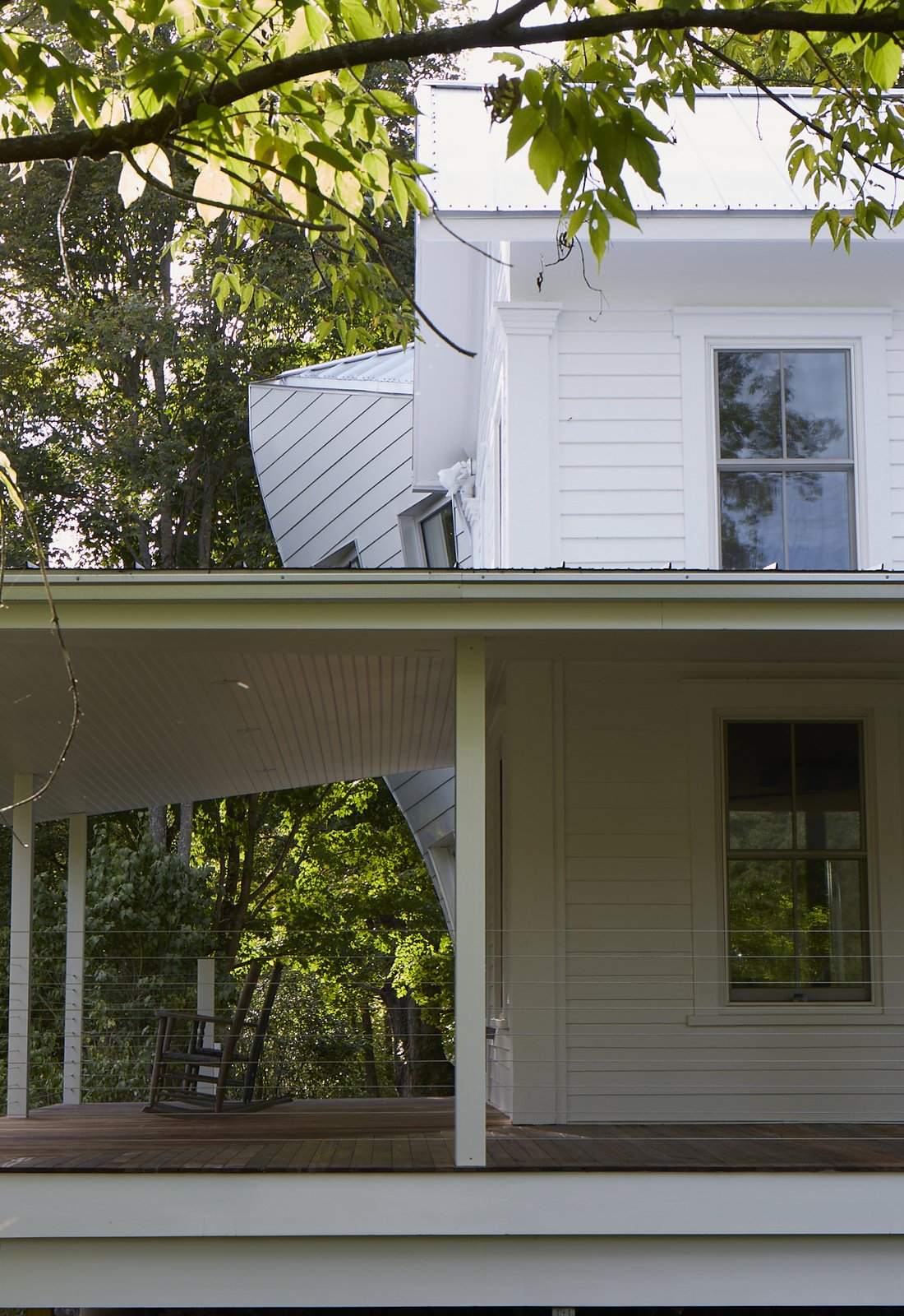 The twisting volume is glimpsed from the road, confusing and delighting the locals, as it peaks out beyond the deep covered porch.  twist farmhouse