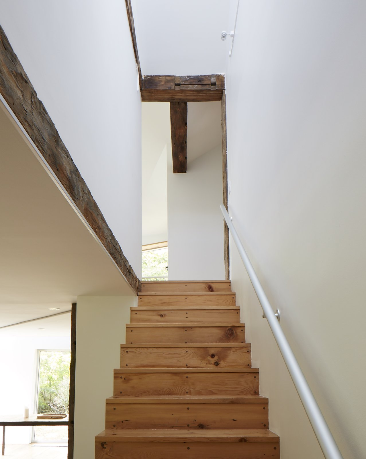 An anodized aluminum handrail and original exposed beams in the vaulted stairwell. The minimalist staircase is crafted from the farmhouse's original wall planks.  twist farmhouse