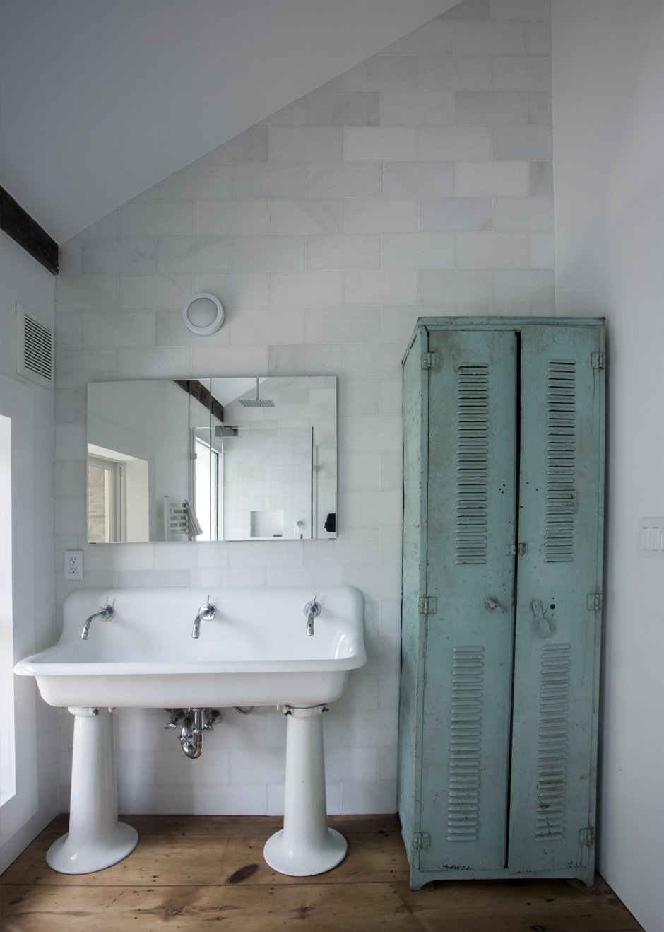 Quartz tile and original plank floors surround a 1920's schoolhouse sink in the vaulted second floor bathroom. The sink's original tap openings were enlarged to accommodate modern Jado faucets, and the entire sink was re-glazed. Old turquoise locker found in a barn in upstate NY.  twist farmhouse