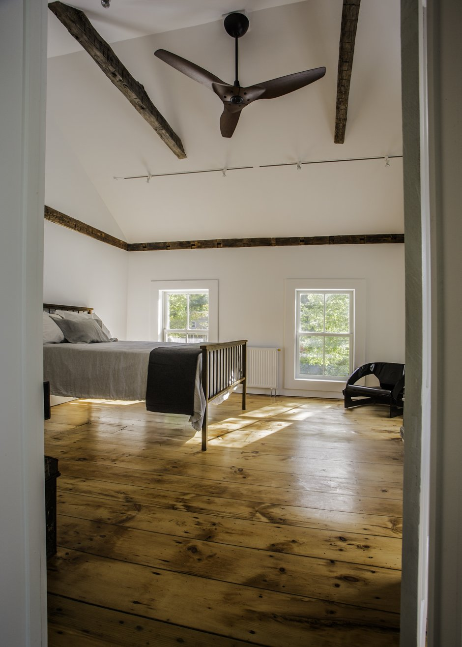 Salvaged hand hewn ceiling beams complement the original beams now exposed along the entire perimeter of the walls in the master bedroom. Ceiling fan by Haiku.  twist farmhouse