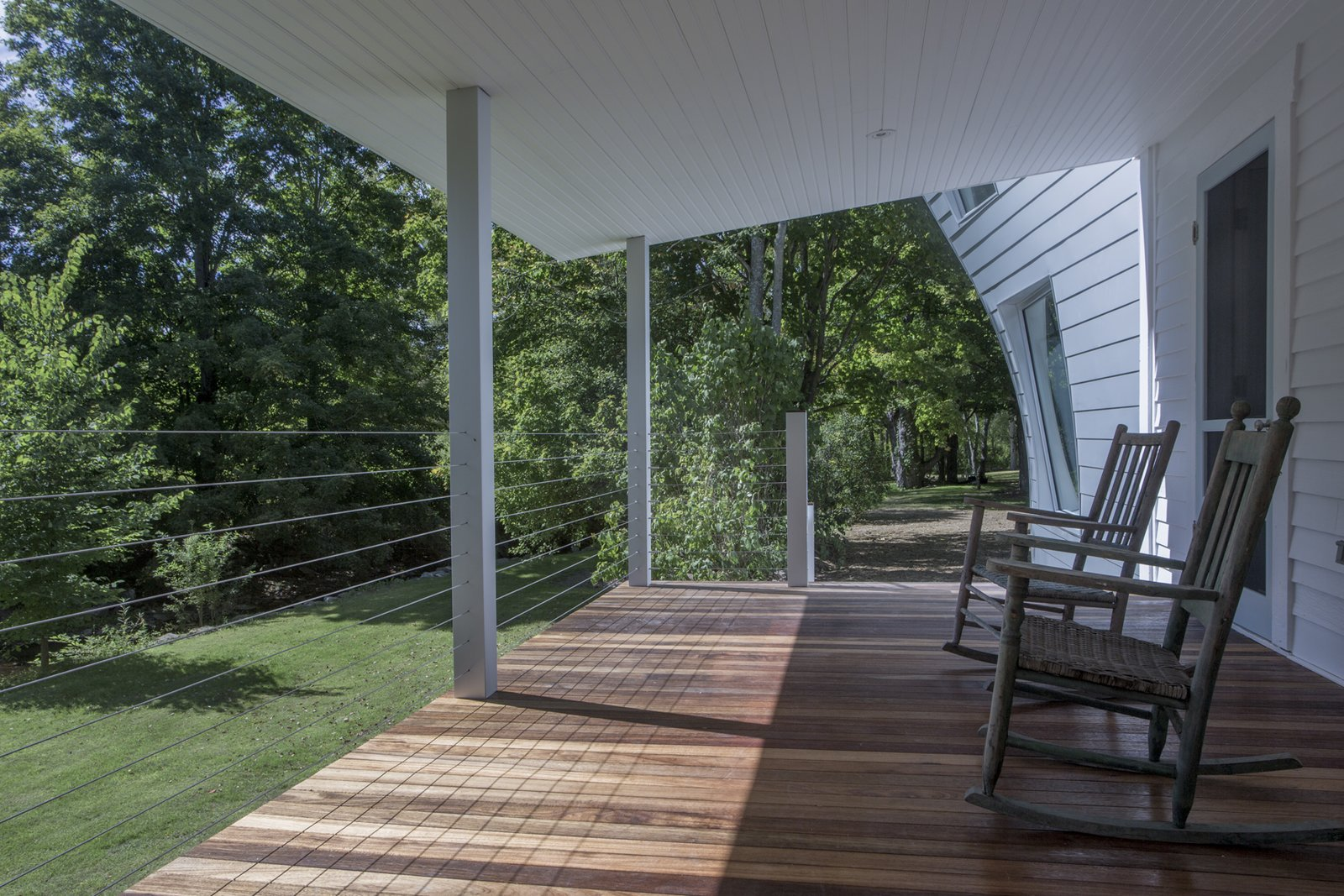 Anodized aluminum porch columns match the addition siding, and stainless steel cables, virtually invisible, maximize the creek side views. Mahogany floors and bead board ceilings complement the farmhouse's original clapboard siding.  twist farmhouse