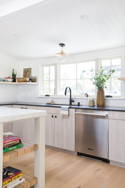 Amber Lewis's chic kitchen features a white undermount sink and a matte black faucet.  Cooking Up Style by Dwell