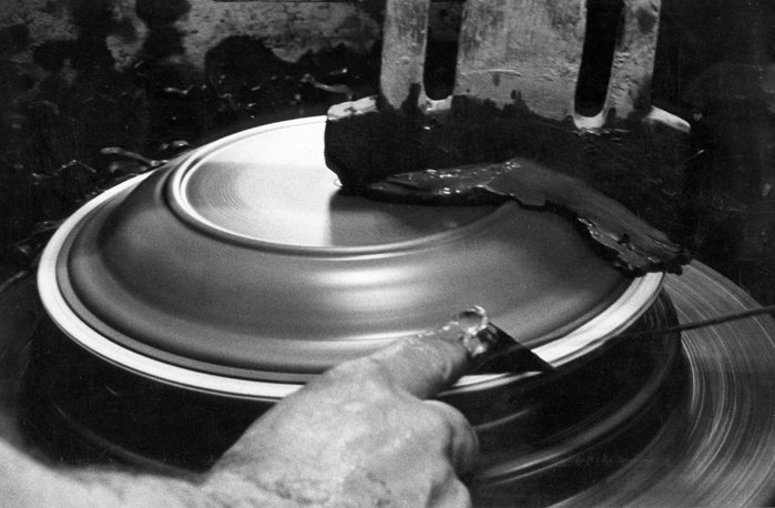 This in an archival photograph showing a plate being formed in the 1950's on a manual jiggering machine.  Photo 6 of 36 in Sausalito Dinnerware Factory Tour