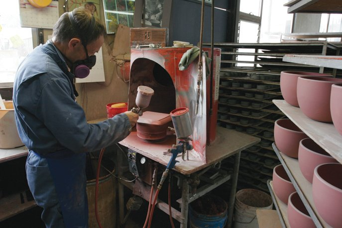 Glaze is applied to the pieces by hand with a spray gun.  Photo 25 of 36 in Sausalito Dinnerware Factory Tour