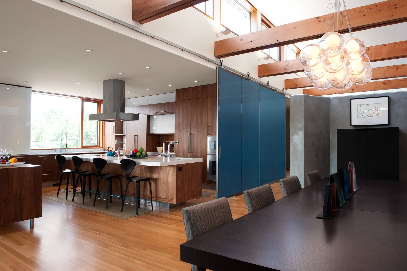 DECA Architecture designed a moveable wall to create a guest area when closed, and join the space with the kitchen and dining room when open.  The CYRK Building