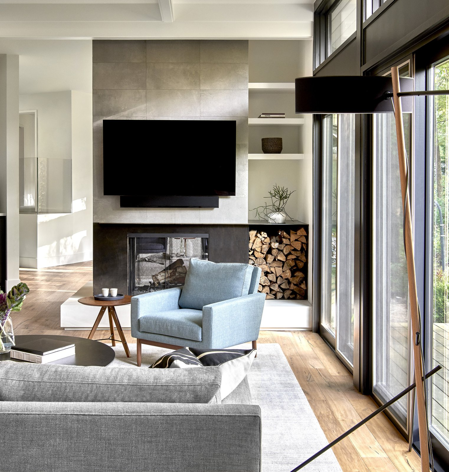 Living Room, Light Hardwood Floor, Chair, Wood Burning Fireplace, and Floor Lighting Double-Sided Fireplace in Family Room  Riverwoods by dSPACE Studio
