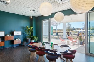 Green wall paint marks the bar area of the tasting room, where Warren Platner-designed chairs from Knoll encircle a Jean Prouve-designed table.