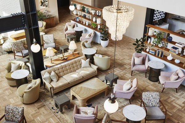 Light-toned parquet floors, a pastel palette, and Murano glass chandeliers contrast with steel structural elements in the living room-like lobby, which offers food and drink service.