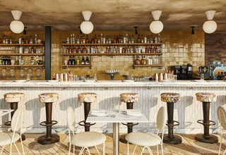 The bar area of Summerly, the rooftop bar and restaurant, displays brass stools upholstered with floral-patterned fabric, geometric tile, and cafe tables and chairs.