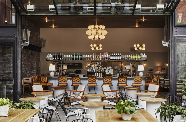 Backyard, the hotel's casual outdoor restaurant, is framed with blackened steel and brick structural elements that reference the neighborhood's industrial past.