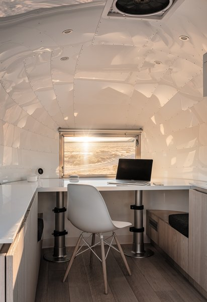 At just 80 square feet, The Kugelschiff is a renovated Airstream Bambi II that now serves as a tech entrepreneur's tiny home and office. Edmonds + Lee Architects designed a desk set on pistons that converts to a bed, creating a smart home office idea for small spaces.