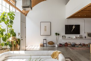 Raw concrete floors and wood beams and arches provide an industrial aesthetic in the loft, where designer Sally Breer arranged a custom sofa covered with linen cotton and a Laurel brass floor lamp. The lightning bolt painting is by Breer's mother.