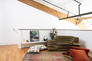 """Breer placed an Ubald Klug-designed Terrazza loveseat by de Sede in the corner of the bedroom area. The rug is vintage. """"I'm a rug hoarder,"""" the designer says. """"I'm constantly buying vintage rugs and am embarrassed to admit how many I've in storage."""""""
